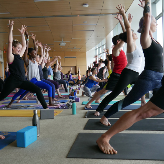 Create Karma participants in warrior one yoga pose during a community class.
