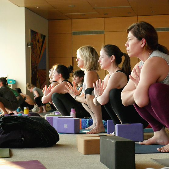 Create Karma participants sit in the goddess yoga pose.