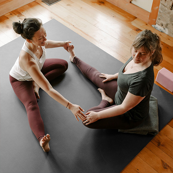 Sarah Yukie assists her student in a yoga pose.